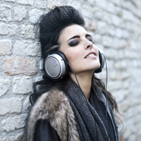 informal-young-woman-listening-to-music-near-grunge-wall-3771823